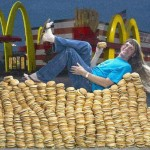 A man chilling on his bed made of hamburgers